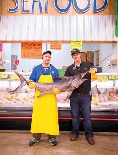 Sam Detwiler & seafood manager Dave Holman showing off their fresh Swordfish.